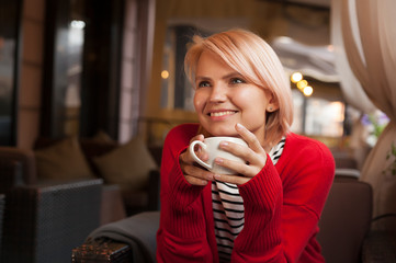 young beautiful girl drinks tea from a white mug, young blonde drinks coffee in a cafe, outdoor cafe