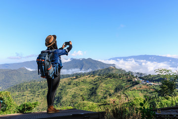 backpack tourists asia women girl using cellphone take pictures landscape on the mountain Thailand