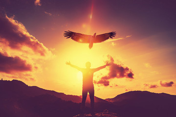 Man raise hand up on top of mountain and sunset sky with eagle bird fly abstract background. Wall mural