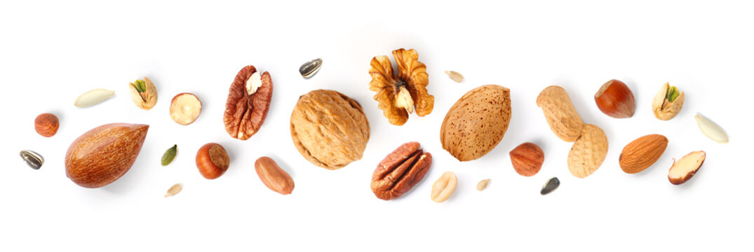 Creative layout made of hazelnut nuts, almonds, walnut, peanut, pecan, sunflower seeds on white background. Flat lay. Food concept.