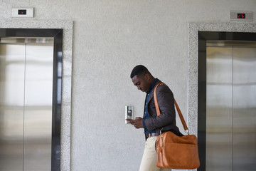 Young professional man texting while walking