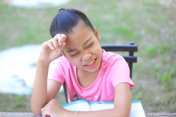 Asian little girl reading a book and sitting ,Reading the book with intention are Preparing for the examination.