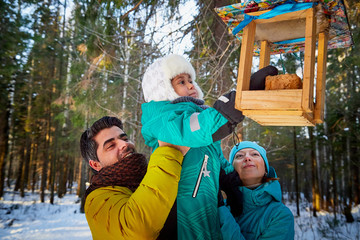 Happy family walking in a winter forest