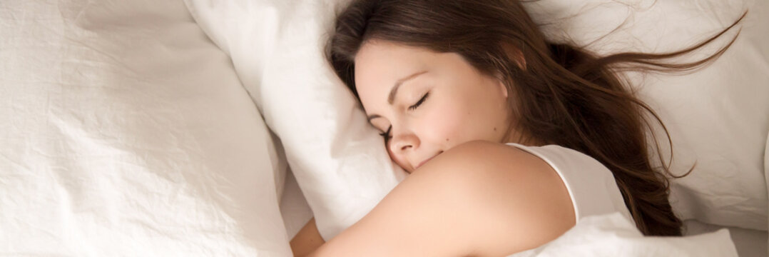 Above panoramic view young woman sleeping in bed hugging pillow