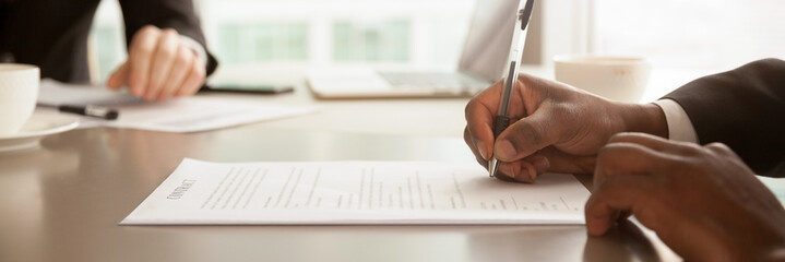 Horizontal closeup image black businessman sitting at desk signing contract