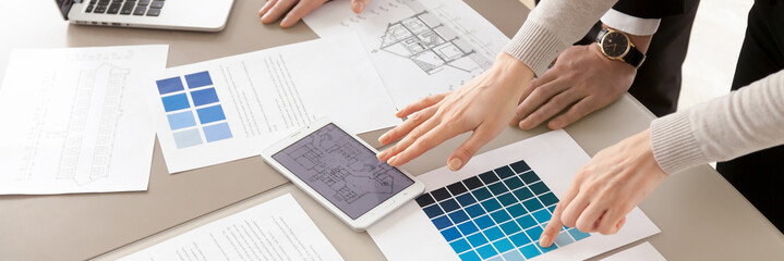 Closeup interior designers working with color swatches palette and blueprint