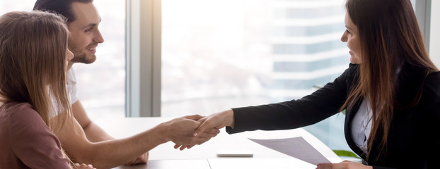 Horizontal image couple signing real estate contract handshaking with realtor