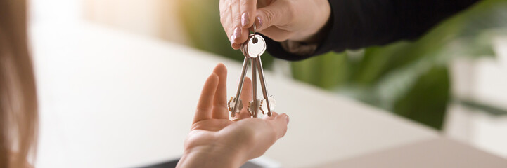 Horizontal image close up male hands giving keys to female