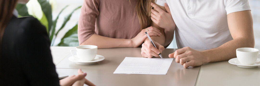 Married couple signing rental agreement sitting at desk with realtor