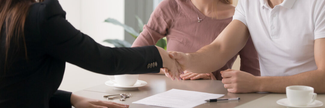 Horizontal photo couple signing real estate contract handshaking with realtor