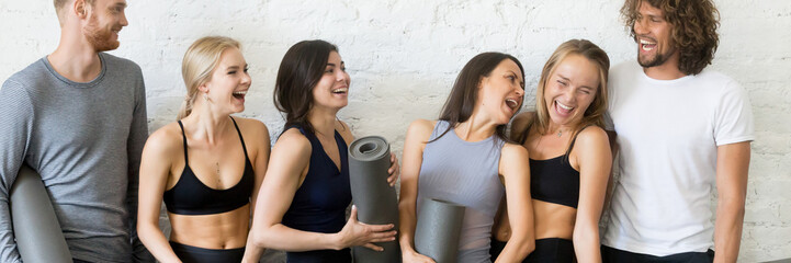 Laughing people resting after workout standing in row near wall