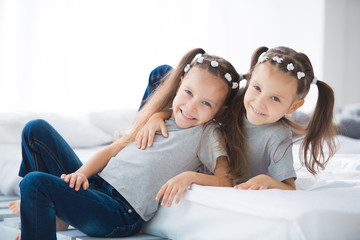 Two little cute smiling girls sisters twins are sitting on the bed in the room