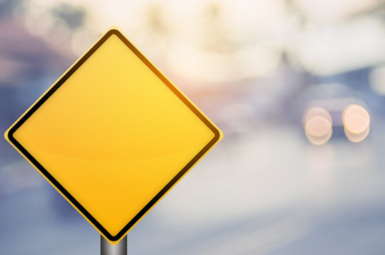Empty yellow traffic sign on blur traffic road with colorful bokeh light abstract background.