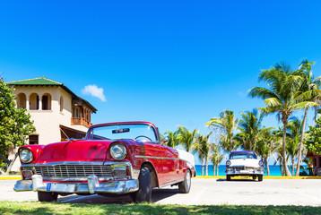 Roter amerikanischer Cabriolet  Oldtimer und ein blau weisser Oldtimer parken am Strand von Varadero in Cuba - Serie Kuba Reportage Wall mural