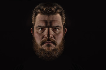 Close-up portrait strong serious brutal bearded man on black. Confident and dramatic concept