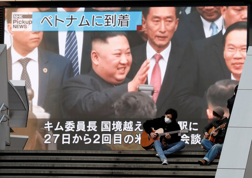 Men play guitars in front of a huge screen broadcasting North Korea's leader Kim Jong Un's arrival in Vietnam for the upcoming summit with U.S. President Donald Trump, in Tokyo