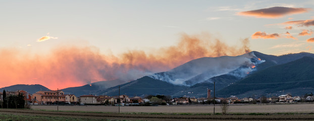 Overview of Mount Pisano in flames at sunset from Bientina, Tuscany, Italy