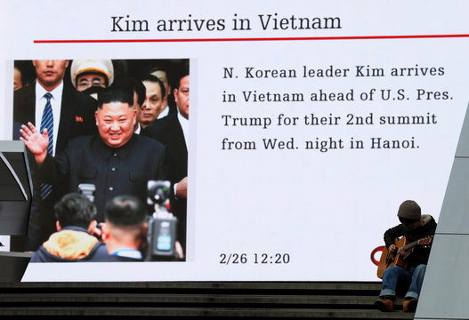 Man plays guitar in front of a huge screen broadcasting North Korea's leader Kim Jong Un's arrival in Vietnam for the upcoming summit with U.S. President Donald Trump, in Tokyo