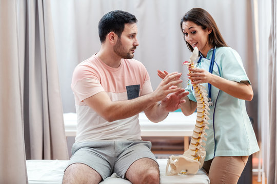 Female doctor in uniform holding spine bodel and talking to patient while patient showing her where he feeling pain.