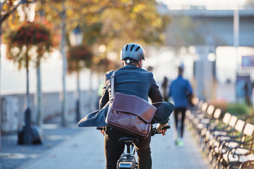 A rear view of businessman commuter with electric bicycle traveling to work in city. Wall mural