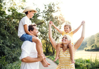 Young family with small children in sunny summer nature.