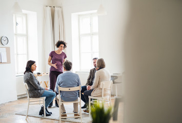 Young woman standing and talking to other people during group therapy.