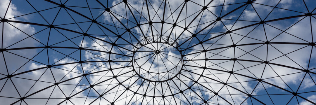 Bottom view of an iron structure with blue sky and clouds in the background
