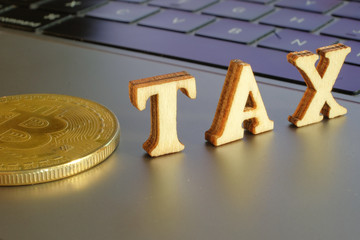 Bitcoin  and next to wooden with TAX letters. Bitcoin taxation concept