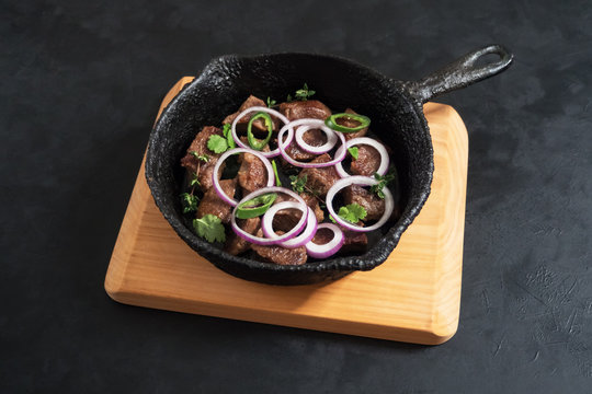 Pieces of roast beef in an old black pan.