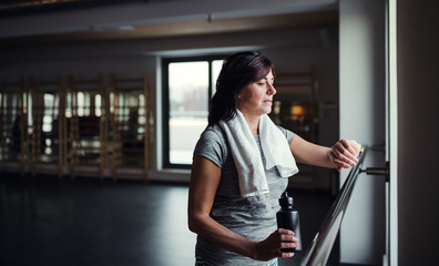 A senior woman in gym resting after doing exercise. Copy space.