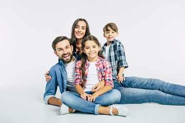 Children is a gift. Photo of beautiful smiling family in casual clothes lying together isolated on white