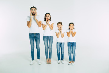 Shocked and surprised beautiful family in t-shirts standing in line looking on camera isolated on white background