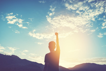 Copy space of man rise hand up on top of mountain and sunset sky abstract background.
