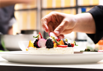 Chef in cuisine prepars cheesecake with fruits