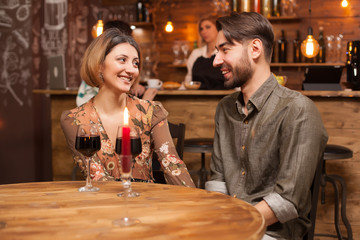 Handsome bearded man laughing with his girlfriend on their romantic date