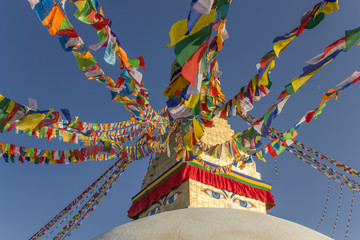 Boudhanath Tibetan Buddhist Stupa with colorful prayer flags against a clear blue sky