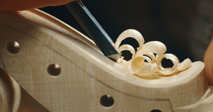 Macro close up of professional master artisan luthier painstaking detailed work on wood violin in a workshop.