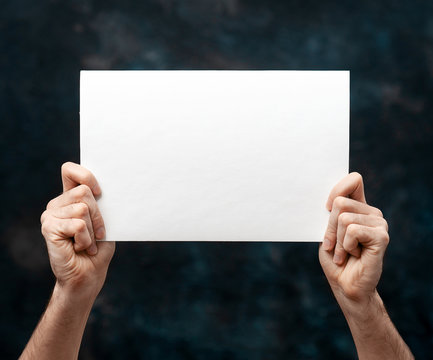 Hands holding blank white paper isolated over black