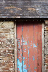 The distressed red wooden door of an old barn in the countryside