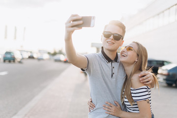 Capturing bright moments. Joyful young loving couple making selfie on camera while standing outdoors