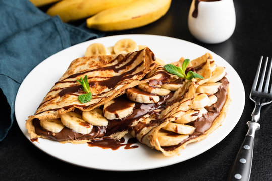 Tasty crepe with hazelnut chocolate spread and banana on white plate
