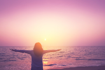 Wall Murals Candy pink Copy space of woman rise hand up on sunset sky at beach and island background.