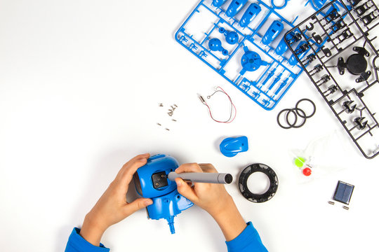 Child hands making blue robot. Robotic, learning, technology, stem education for children background