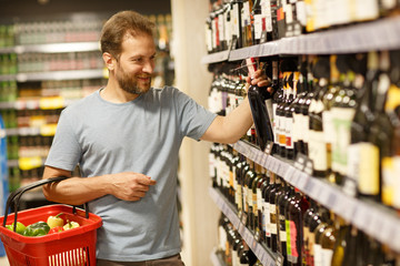 Handsome man standing near shelves with alcohol in supermarket and choosing products. Bearded client of store holding red basket in one hand and taking bottle of wine with another hand.