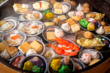 Traditional Asian dishes steamed in a bamboo basket - vegetables, mushrooms, shrimps, dough. Street food.