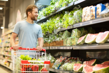 Customer smiling and standing in supermarket, holding hands on trolley full of products. Bearded man looking away at shelves with salad, watermelon and other vegetables.