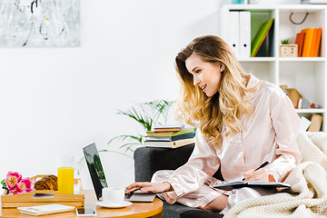 Smiling woman in pyjamas writing in notebook and using laptop at home