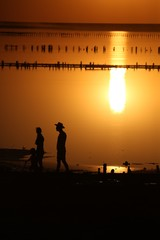 On a salt lake in the setting sun, family, father with a hat, mother and small child on the horizon with a silhouette walk along the shore