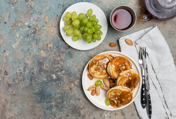 Shrovetide Maslenitsa Butter Week festival meal. Stack of pancakes blini with caramel with nuts, green grape, tea. Russian style, close up top view