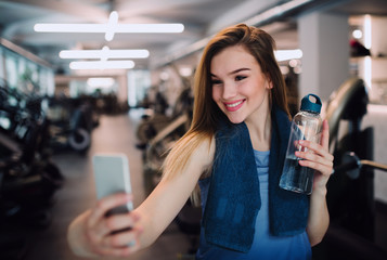 A portrait of young girl or woman with smartphone in a gym, taking selfie.